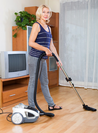 vaccuum: cheerful  mature woman cleaning with vacuum cleaner on parquet floor at home