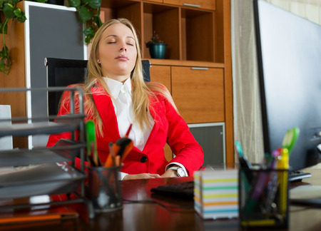 complications: Young blonde girl sleeping in office chair Stock Photo