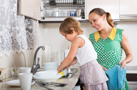 Little serious girl helping mother washing dishes in the kitchen. Focus on girl