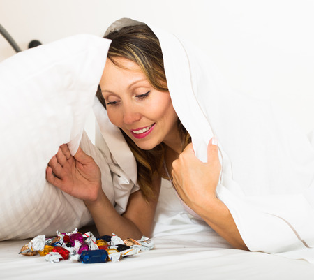 furtively: Happy smiling adult woman laying in bed with sweets in secret