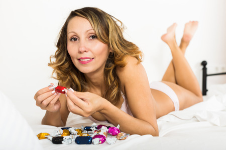 lier: woman with chocolate candy resting on the bed