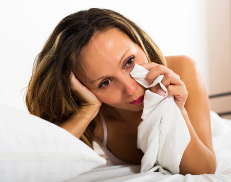 downcast: Portrait of thoughtful female with downcast eyes in bed Stock Photo