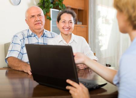 empleada domestica: Sonriente pareja de ancianos hablando con los empleados con el portátil en casa. Centrarse en la mujer