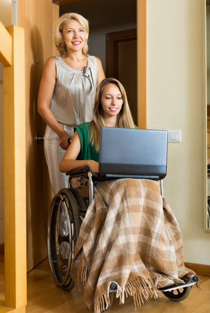 incapacitated: Happy woman in wheelchair with female assistant working on laptop Stock Photo