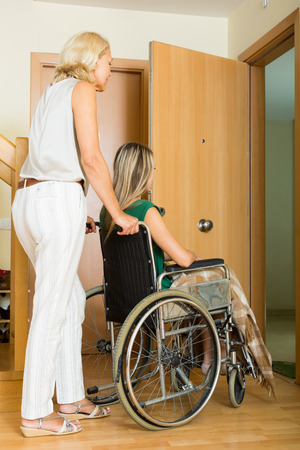 incapacitated: Elderly mother helping handicapped girl to enter the apartment
