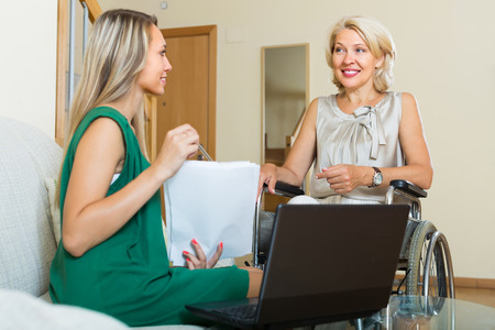 incapacitated: Social worker with laptop questioning handicapped woman. Focus on mature Stock Photo