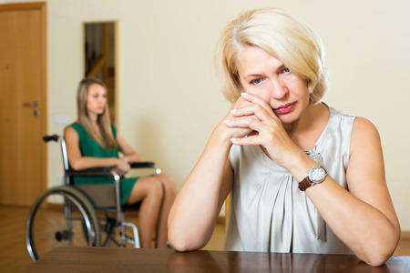 incapacitated: Tired mature woman and disabled person on chair indoor