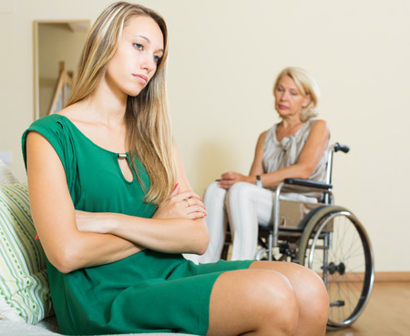 sad woman and handicapped female having domestic quarrel photo