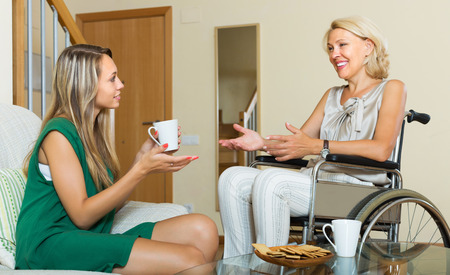 incapacitated: Female friend visiting positive disabled woman on chair indoor Stock Photo