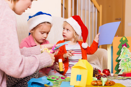 4s: woman with two girls preparing for Christmas at home together Stock Photo