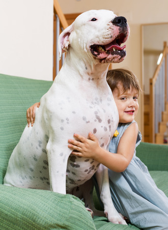 Nice girl toddler on couch with dogo Argentino (focus on dog) photo