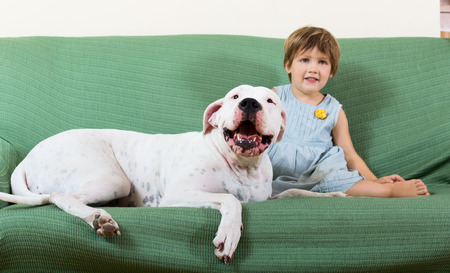small nice girl on couch with dogo Argentino (focus on dog) photo