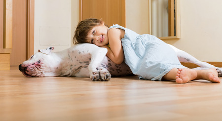little nice girl on the floor with dogo Argentino photo