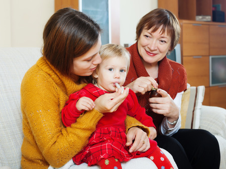sick baby: Young mother with mature grandmother giving  medicament to sick baby  at home Stock Photo