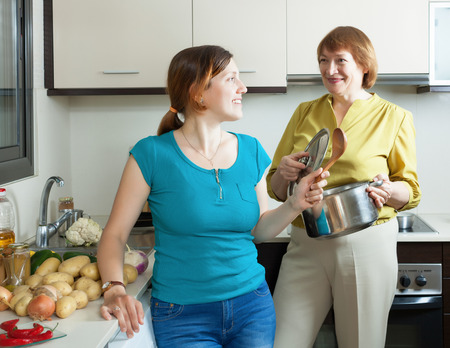 multi generational: Positive young woman and mature mother cooking lunch in kitchen at home