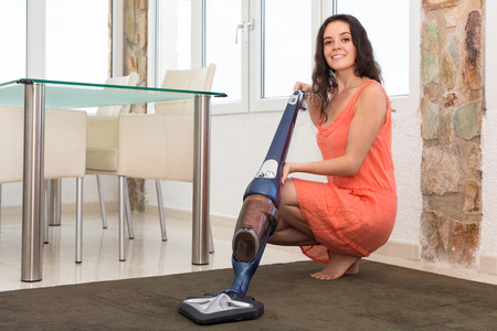 Photo of smiling young female in dress vacuuming living room photo
