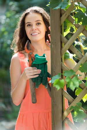 pruning scissors: Smiling female florist working with pruning scissors in the garden