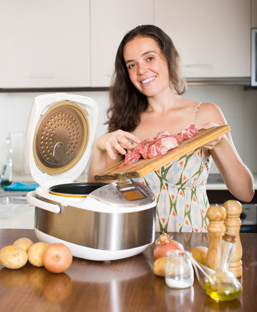 Young smiling housewife cooking meat with electric multicooker at home photo