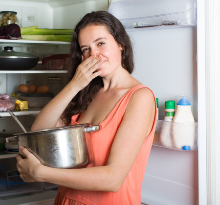 frowy: Young housewife holding foul food near refrigerator at home Stock Photo