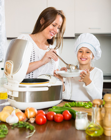 Slow cooker helping mother and girl to prepare dinner at home kitchen