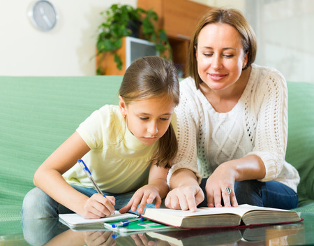 mother and teen daughter: schoolgirl and mother together doing homework in home
