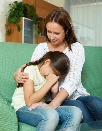 Woman comforting  crying daughter at home photo