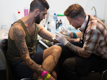 BARCELONE, ESPAGNE - 3 octobre 2014: Artiste professionnel faisant tatouage sur le bras de client. La 17e édition de l'Expo Barcelona Tattoo