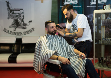 BARCELONA, SPAIN - OCTOBER 3, 2014: Professional hairdresser shaving back of the mens head. The 17th edition of The Barcelona Tattoo Expo in Fira de Barcelona.
