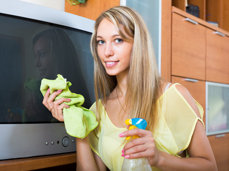 tele: Blonde young smiling girl cleaning TV with cleanser at home Stock Photo
