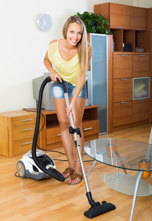 vaccuum: Blonde  woman in shorts cleaning with vacuum cleaner on parquet floor at home