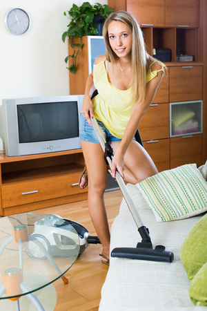 vaccuum: Full length shot of young smiling woman with vacuum cleaner at home