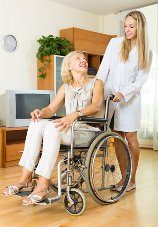 incapacitated: Happy woman in wheelchair with medical assistant in room
