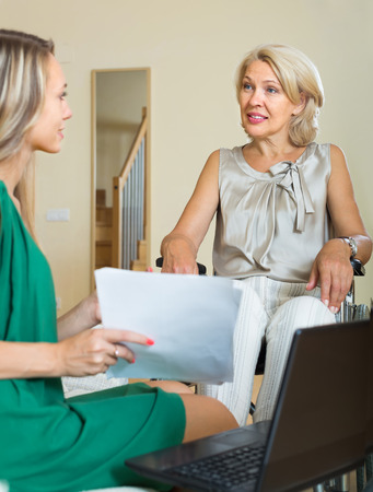 incapacitated: Female social worker with laptop questioning handicapped smiling woman Stock Photo
