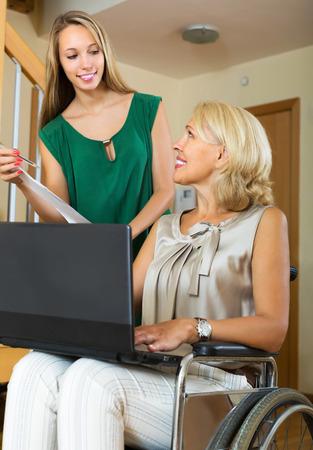 paraplegico: Agente de seguros amable y mujer con discapacidad positivo en silla de interior