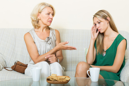 50 to 60 years: Adult daughter and mature mother having serious talking on sofa