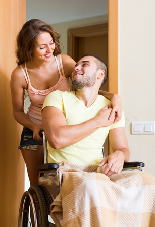the spouse: Happy  russian couple with spouse in wheelchair near apartment entrance Stock Photo