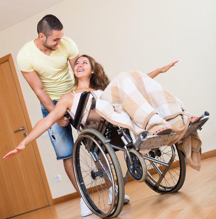 Gelukkig paar met lachende echtgenoot op rolstoel in speelse bui in huis