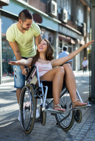 spouse: Husband taking happy spouse on wheelchair in playful mood outside