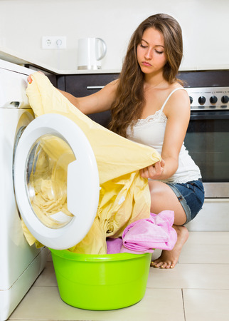 Home laundry. Sad young woman with clothes near washing machine at home photo
