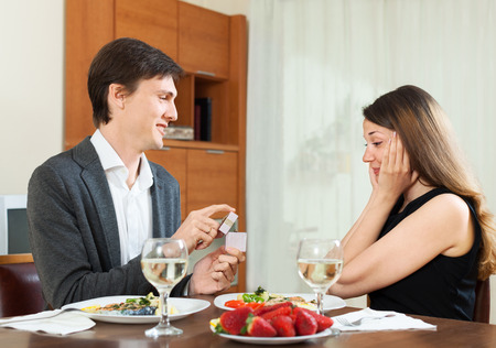 Man giving to girl gold ring box  at home photo