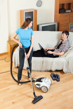vaccuum: Girl doing room cleaning with vaccuum cleaner while man  with laptop  resting over sofa