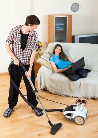 disparity: Handsome man doing cleaning during girl with notebook resting over sofa at home