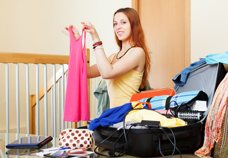 young add: european woman choosing clothes for vacation  at home Stock Photo