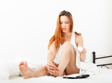 nail scissors: beautiful woman caring for toes with cosmetic cream in bed Stock Photo