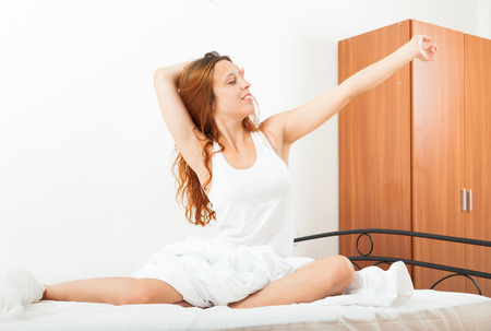 awaking: red-haired  woman awaking up on white sheet in bed at home