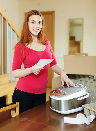 slow cooker: cheerful woman  reading guarantee card for new slow cooker at home Stock Photo