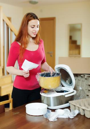 cheerful woman unpacking and reading manual for new crock-pot at home interior photo