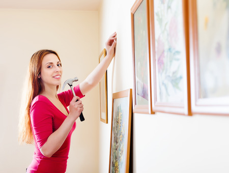 parade of homes: Smiling  woman hanging  art picture on wall at home