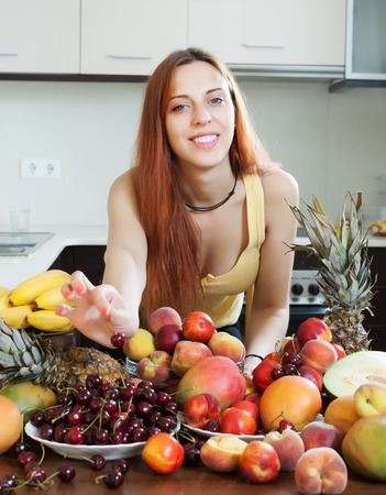 Happy young housewife with ripe fruits at domestic kitchen photo