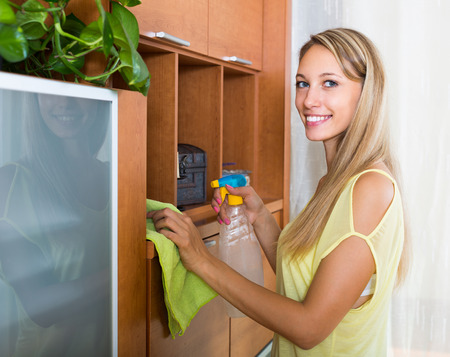cleanser: Young brunette woman dusting wooden furniture with rag and cleanser at home